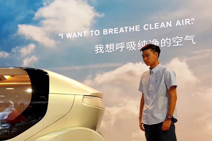 Eine Projektion zeigt auf dem Foto eines Wolkenhimmels den Text: «I want ro breathe clean air» auf Englisch und Chinesisch. Davor ein junger, nachdenklich schauender Mann.