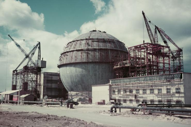 Farbfoto in deutlich antiquiertem Kolorit zeigt die Baustelle des Atomkraftwerkes, der Kühlbehälter ist kugelrund.