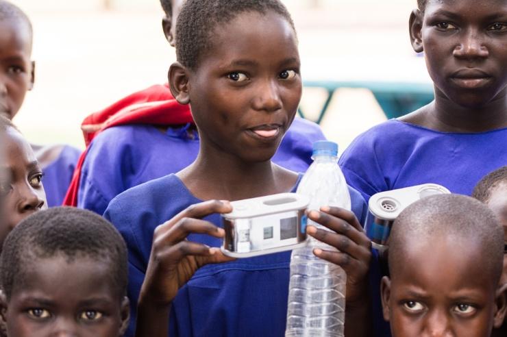 Ein Mädchen mit dem Wadi und Trinkflasche in der Hand blickt keck in die Kamera.