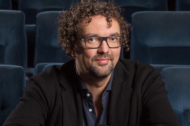 Filmemacher Trimpop mit Locken und großer Brille sitzt in einem leeren Kinosaal und blickt in die Kamera.