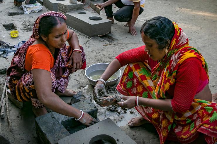 Zwei Frauen in indischer Kleidung bauen einen Lehmherd