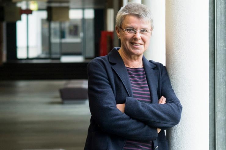 Ingrid Schmale steht lächelnd und mit verschränkten Armen auf einem Flur