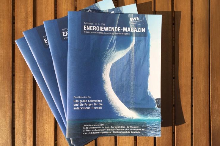 Vier Print-Ausgaben des EWS Energiewende-Magazins liegen aufgefächert auf einem Holztisch.