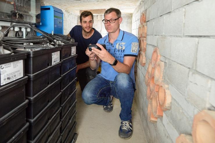 In einem Keller stehen Salzwasserbatterien, darüber sind Steuerungskästen montiert; im Hintergrund schauen zwei Männer auf ein Display.