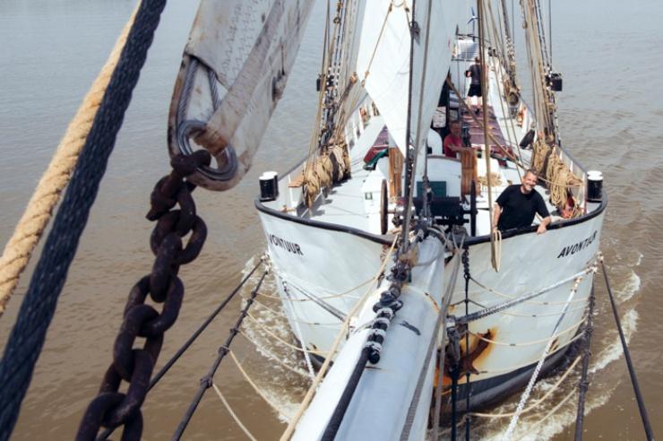 Aufnahme eines Segelschiffes vom Bugspriet aus; von der Reling her grinst ein Mann gutgelaunt in die Kamera.