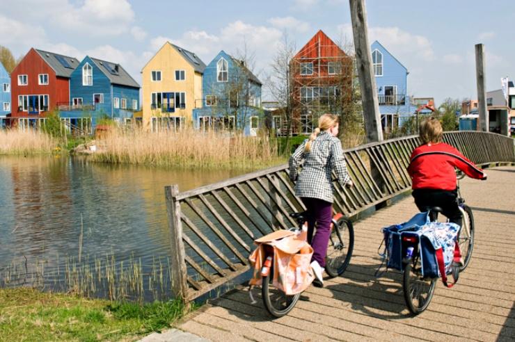 Blick über eine Brücke zur Siedlung mit bunten Häusern