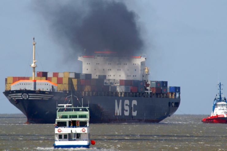 Containerschiff mit schwarzem Dieselqualm