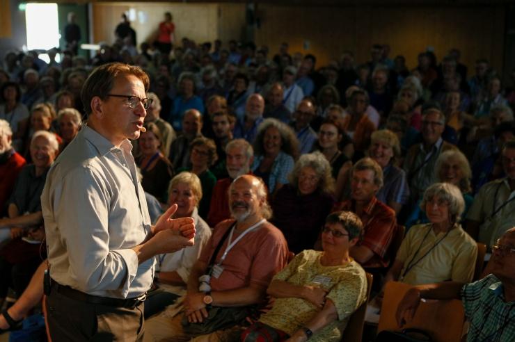 Prof. Jörg Probst im Vordergrund, vergnügtes Publikum im Hintergrund