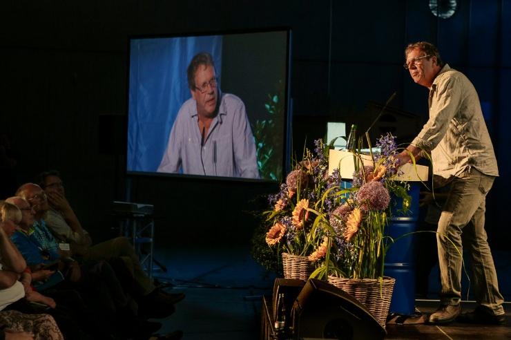 Georg Schramm steht auf der Bühne, links im Hintergrund die Video-Übertragung.