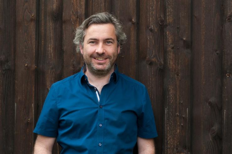 Porträt von Alexander Sladek vor einer dunkelbraunen Holzwand