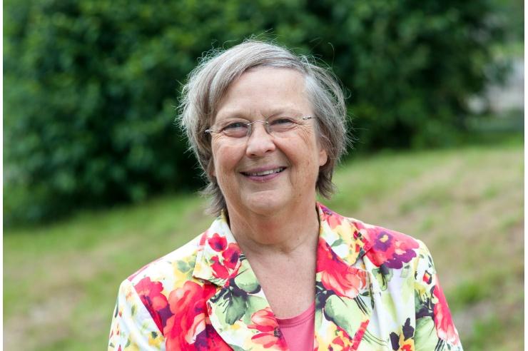 Bärbel Höhn, in geblümtem Jacket im Grünen stehend, lacht in die Kamera.
