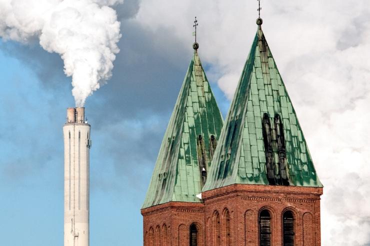 Zwei Kirchturmspitzen davor ein hoher qualmender Schornstein.