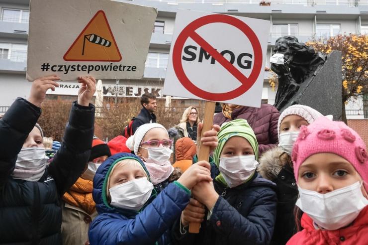 Kinder vor einem Wohnhaus demonstrieren mit Schildern und Atemmasken.