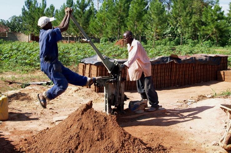 Zwei Männer bedienen die Ziegelpresse, vor ihnen ein Sandhügel, hinter ihnen die gestapelten Ziegelsteine.