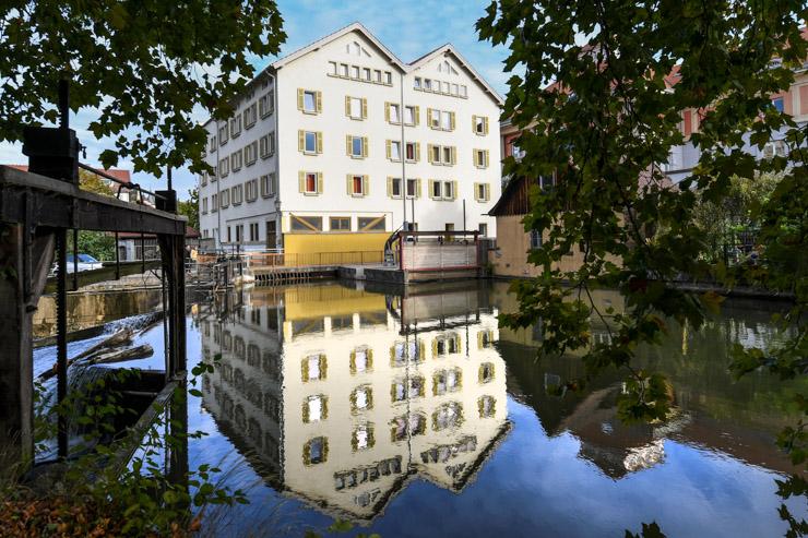 Ein großes Haus mit zwei Satteldächern spiegelt sich im Wasser.