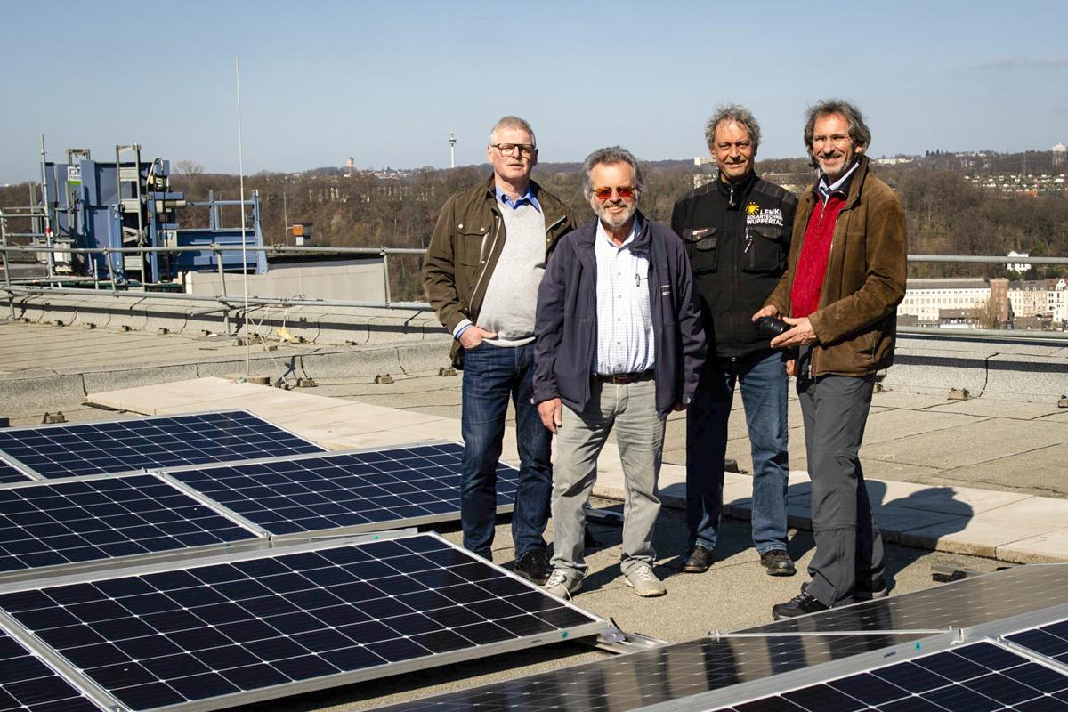 Vier Männer stehen auf einem Dach hinter einer Reihe PV Modulen.