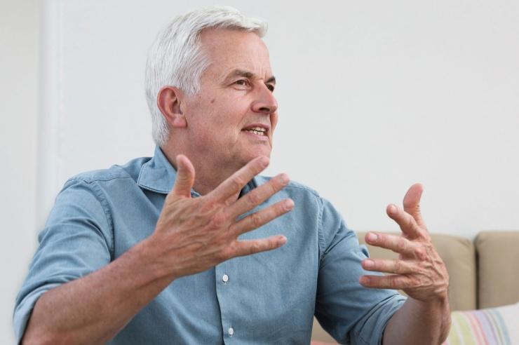 Ein gutaussehender grauhaariger Mittfünfziger gestikulierend im Gespräch.