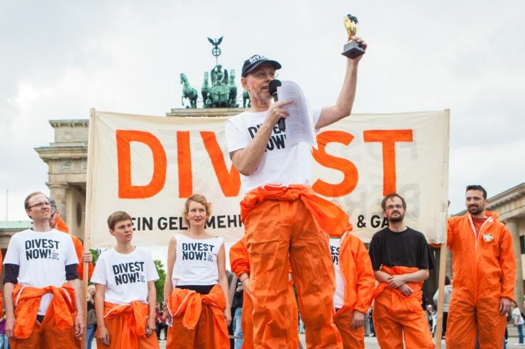 """Vor dem Brandenburger Tor stehen Menschen in orangenen Overalls vor einem """"Divest""""-Transparent. Ein Mann spricht in eine Mikrofon und hält eine Art Pokal in die Luft."""