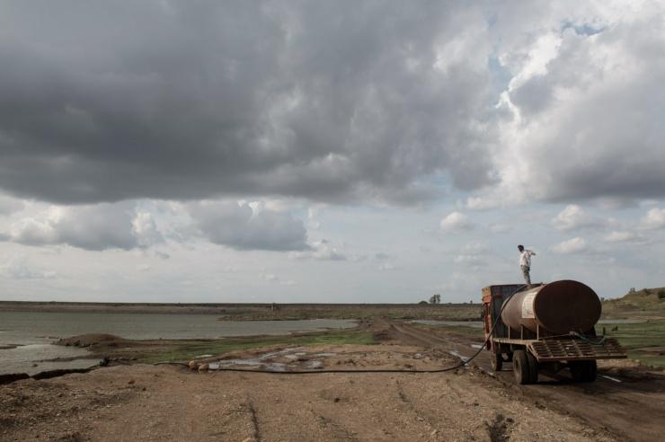 Ein Tankwagen steht mit einem Schlauch im Wasser an einem fast leer gepumpter See.