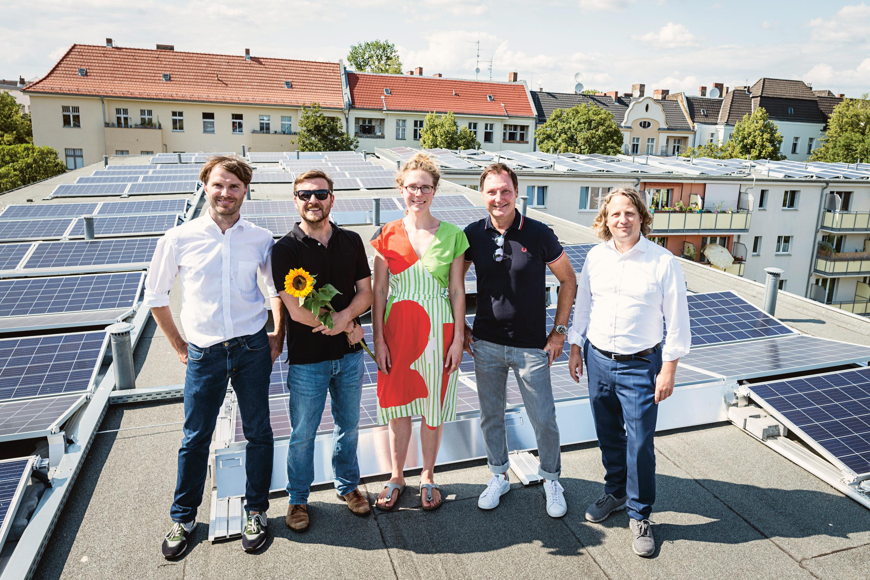 Gruppenfoto auf dem Dach vor den PV-Anlagen: Drei Männer und eine Frau