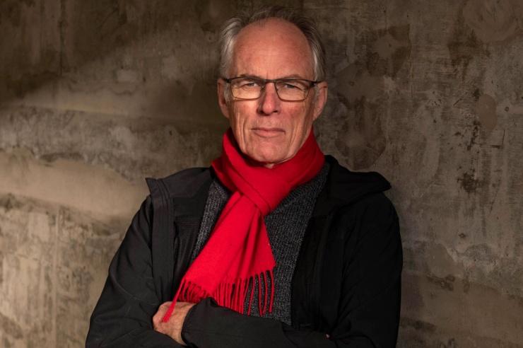 Älterer attraktiver Mann mit rotem Schal draußen vor einer rostigen Wand fotografiert.