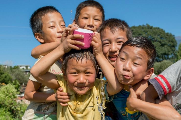Fünf kleine Jungs, eng gedrängt, albern mit einer wassergefüllten Taser herum und lachen in die Kamera.