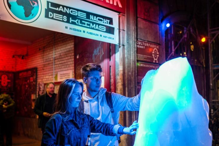 Zwei junge Menschen berühren einen wie ein Eisberg geformten Eisklotz vor dem Eingangsportal zur Langen nacht des Klimas