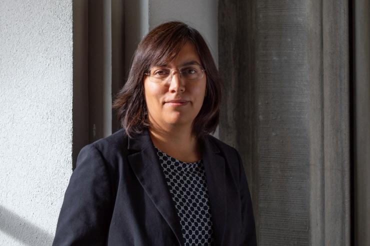 Frau mit Brille und dunklen Haaren vor einer Wand