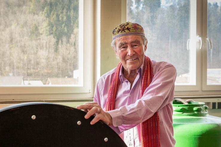 Ein freundlicher älterer Mann mit einer bestickten Kappe auf dem Kopf steht in einer Werkstatt.