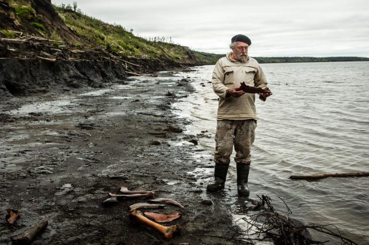 Ein Mann steht an einem Flussufer und hält einen großen Tierknochen in der Hand.