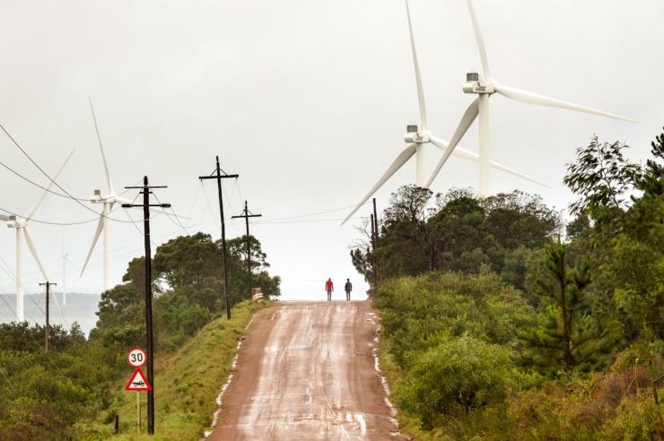 Ein aufsteigender Weg, gesäumt von Windrädern; zwei Menschen sind zentral am Horizont zu erkennen.