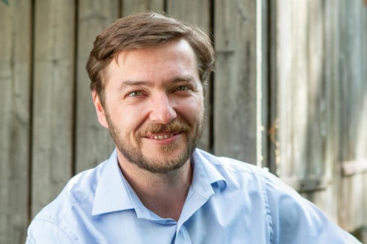 Portrait: Sebastian Sladek vor einer Holzwand
